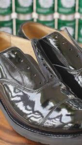 Shiny military dress shoes on a wood pedestal